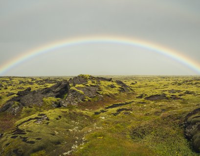 A rainbow hangs over the Iceland tundra